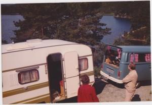 Stord 1980. Vi parkerte vogn i oppkjørselen til Harald og Hjørdis. Gunvor og Sigfred foran vogna. Hans og Gunhild sin vogn Knaus, nesten ny. VW Caravelle. Campingvogna(Knaus) fikk vi låne av Hans og Gunhild - tilbød oss vogna uten at vi spurte. Den var bare to år gammel så det var nifse greier.  Vi hentet deg på Trondsletten. Bilen var blå VW Caravelle. Vi fikk den plassert hos Harald og Hjørdis - fikk den dratt opp til plassen av en liten bil, og måtte snu den for hånd. Bak vogna er det stup på flere meter. Foto: Privat
